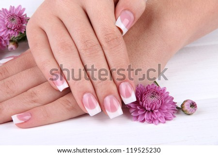 Woman hands with french manicure and flowers on white wooden background - stock photo