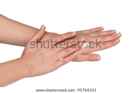 Woman hands with french manicure applying hand cream isolated on white background
