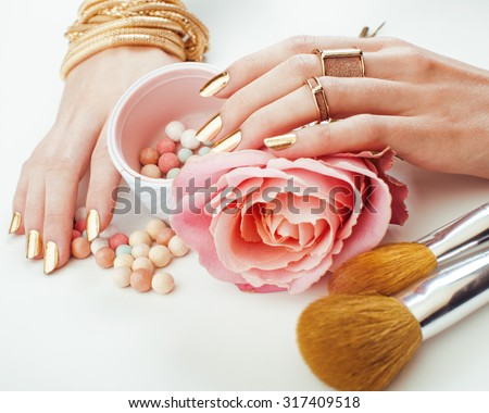woman hands with golden manicure and many rings holding brushes, makeup artist stuff stylish, pure close up - stock photo