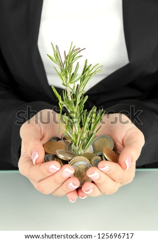 Woman hands with green plant and coins isolated on white