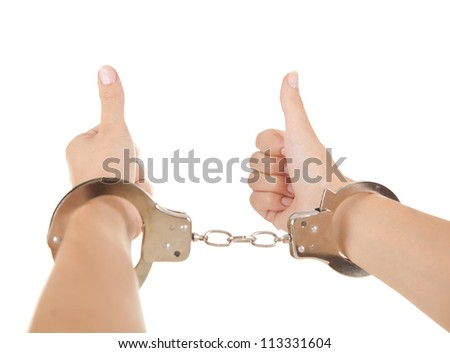 woman hands with handcuffs and thumbs up, white background - stock photo