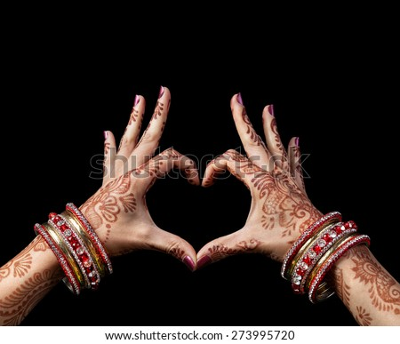Woman hands with henna doing heart gesture isolated on black background with clipping path  - stock photo