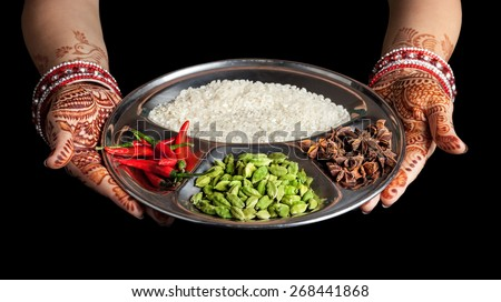 Woman hands with henna holding plate with rice and spices isolated on black background with clipping path  - stock photo