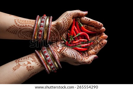 Woman hands with henna holding red chili isolated on black background with clipping path