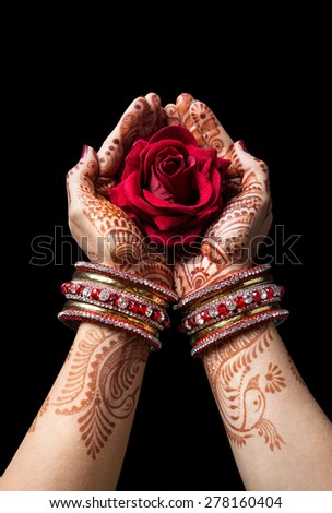 Woman hands with henna holding red rose isolated on black background with clipping path  - stock photo
