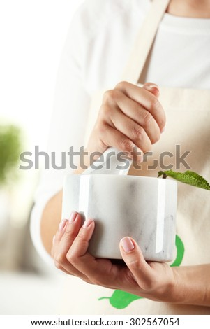 Woman hands with mortar with herbs on bright background - stock photo