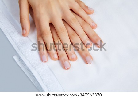 woman hands with nails before treatment on white towel in salon - stock photo