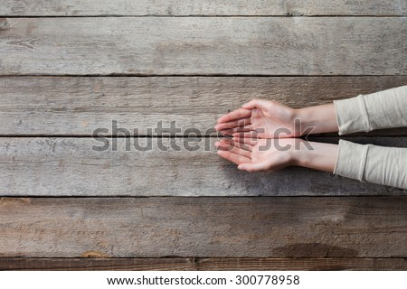 woman hands with open palms over wooden table - stock photo