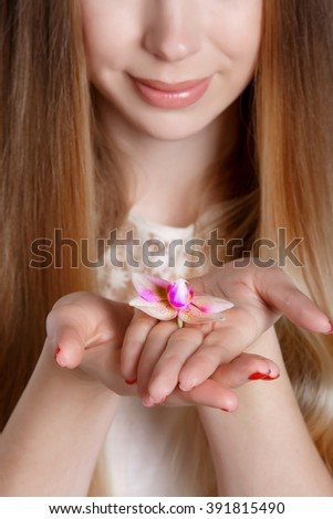 Woman hands with orchid flower skin care and beauty, girl hands with red manicure, closeup. Beautiful young woman holding flower isolated in studio.