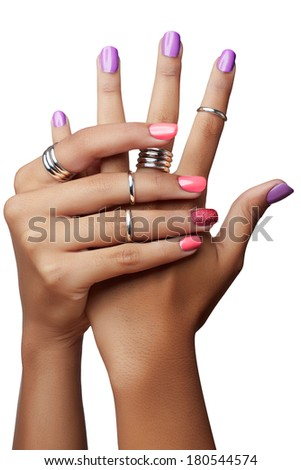 Woman hands with purple and pink nail polish and silver stacking rings on white background - stock photo
