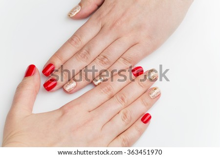 Woman hands with red and gold manicure