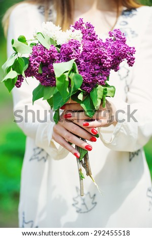 Woman hands with red manicure holding delicate spring lilac flowers bouquet - stock photo