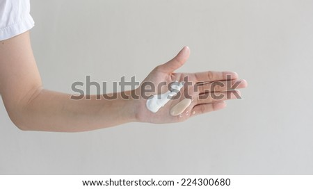 woman hands with skin care cream at wall background