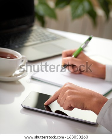 Woman hands with tablet PC and notepad at office - stock photo
