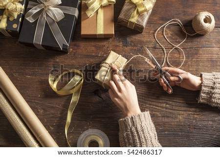 Woman hands wrap gift boxes