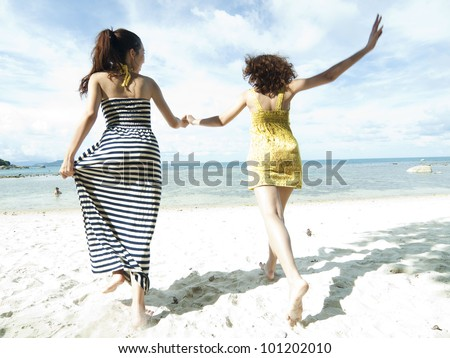 woman hang out  together sand by sea edge on blue sky background