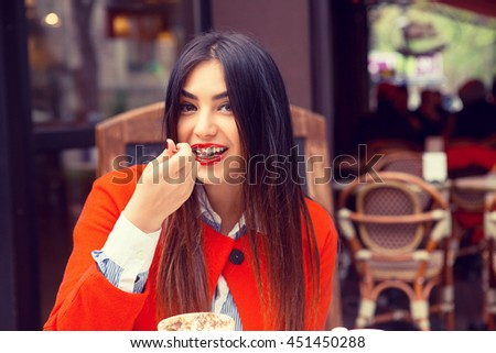 Woman happy eating. Closeup portrait beautiful smiling toothy girl student looking at you camera eating ice cream dessert coffee shop background. Multicultural mixt race. Healthy happy life concept - stock photo