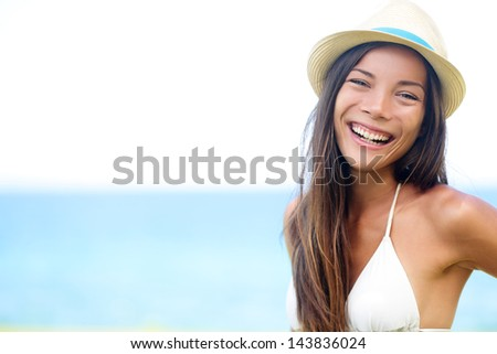 Woman - happy joyful beach summer girl portrait. Laughing lovely smiling multiracial young female model looking excited at camera wearing hipster hat by the ocean sea on sunny summer day by the water. - stock photo