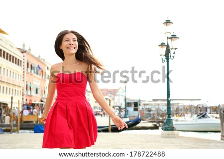 Woman happy running in summer dress, Venice, Italy. Girl smiling laughing joyful having fun by water in Venice. Beautiful multiracial Asian Caucasian young woman cheerful and vivacious. - stock photo