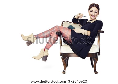 Woman has a good time while sitting on a armchair with a book. - stock photo