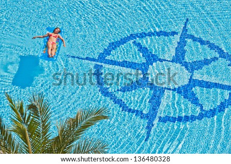 Woman has a rest on inflatable mattress in pool with wind rose image at bottom - stock photo