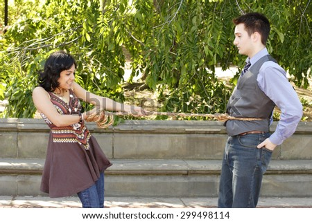 Woman has man on a rope....he doesn't care. - stock photo