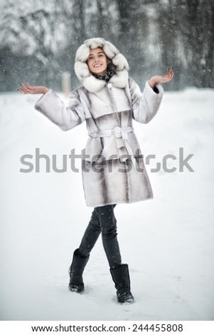 Woman have fun on the snow in winter forest - stock photo
