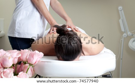 Woman having a back massage in a spa center