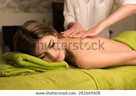 Woman having a back massage in spa beauty center