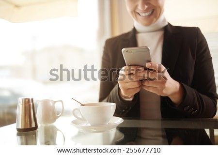 Woman having a coffee and chatting with her touch screen smart phone - stock photo