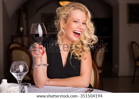 Woman having a glass of red wine  - stock photo