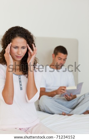 Woman having a headache while her husband is reading - stock photo