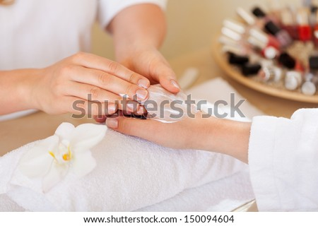 Woman having a manicure and hand massage with the beautician applying hand cream in a spa or beauty salon - stock photo