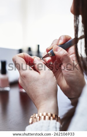 Woman having a manicure and painting her nails