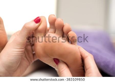 Người phụ nữ có một điều trị chân tại một spa hay thẩm mỹ viện với pedicurist xoa bóp bàn chân.