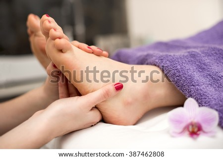 Woman having a pedicure treatment at a spa or beauty salon with the pedicurist massaging feet. - stock photo