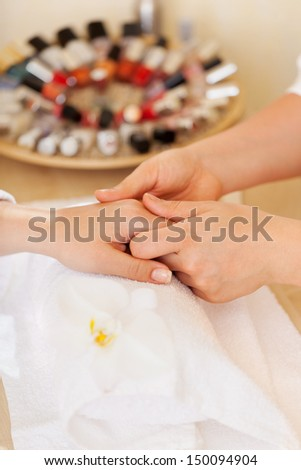 Woman having a spa manicure receiving a hand massage from the beautician with an array of nail varnish in the background - stock photo