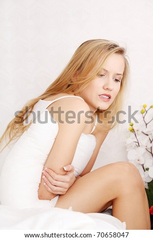 Woman having a stomachache sitting in bed - stock photo