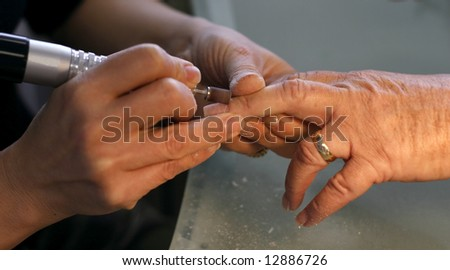 woman having acrylic put on nails