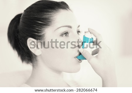 Woman having asthma using the asthma inhaler for being healthy - stock photo