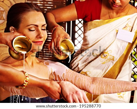 Woman having Ayurvedic spa treatment. Pouring milk. - stock photo