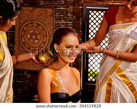 Woman having Ayurvedic treatment. Pouring milk.Spa resorts in India - stock photo