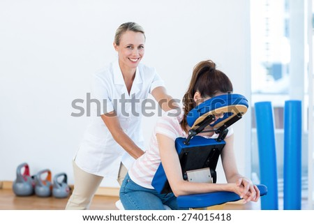 Woman having back massage in medical office - stock photo