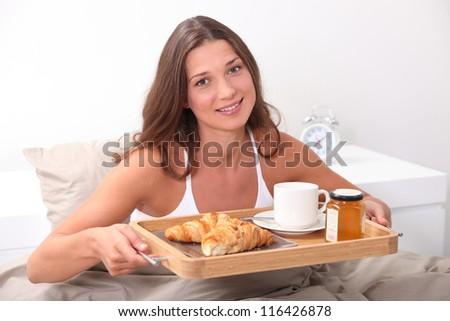 Woman having breakfast in bed - stock photo
