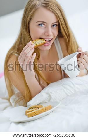 Woman having breakfast in bed. - stock photo