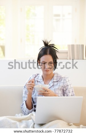 Woman having cereal for breakfast looking at laptop computer, smiling, sitting in living room in pyjama.? - stock photo