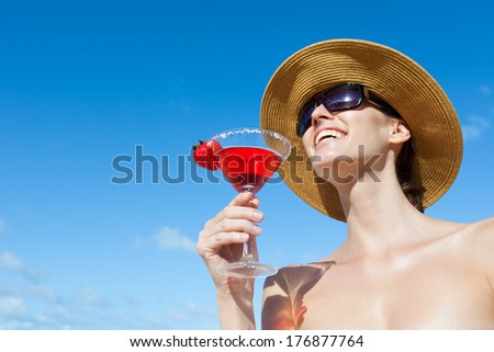Woman having cocktail on the beach. Cocktail party on the beach. - stock photo