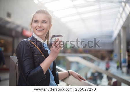 Woman having coffee in shopping center - stock photo