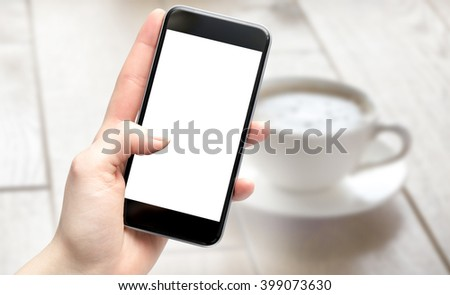 Woman having coffee using her phone in a cafe, filtered with a shallow depth of field - stock photo