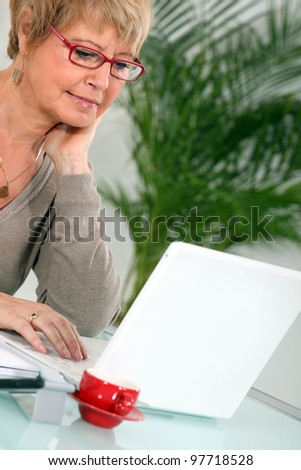 woman having coffee whilst using laptop - stock photo